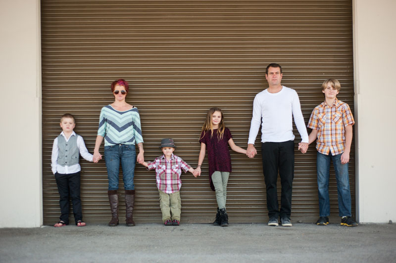 Portrait of Oakland family of six against roll up door