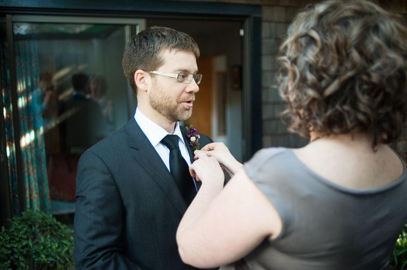 Bride applying boutonniere on Groom in Berkeley