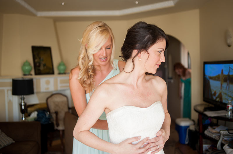 Maid of honor helping bride into wedding dress