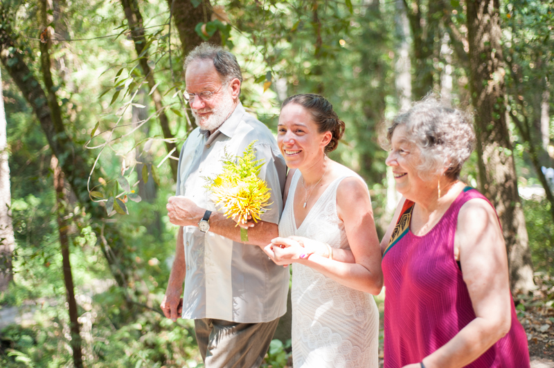 Bride walking down aisle with father and mother
