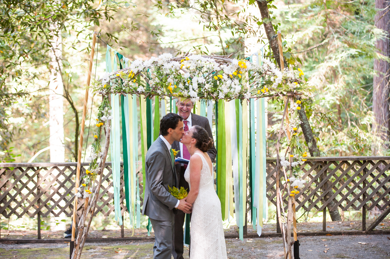 Bride and Groom kiss at wedding ceremony in Griffith Woods