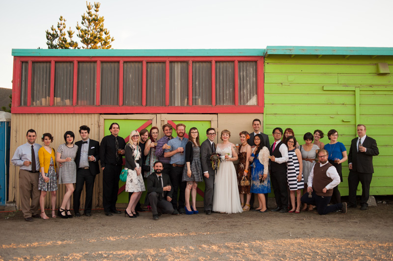 Large group portrait of wedding guests in front of colorful building
