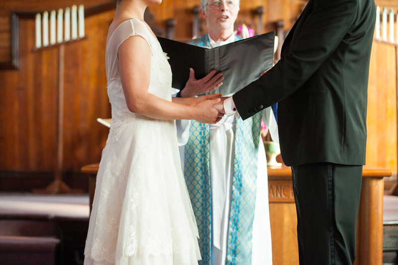 Detail of couple holding hands during ceremony