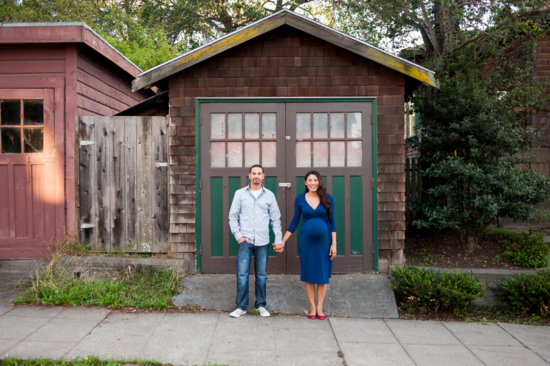 Pregnant couple in front of rustic doors