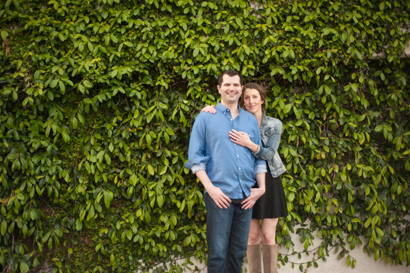 Engaged couple in front of natural wall
