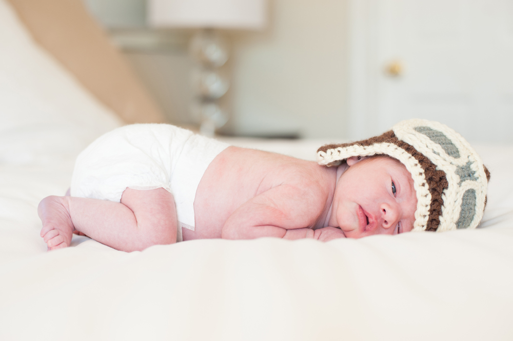 Sleepy newborn wearing knitted aviators hat