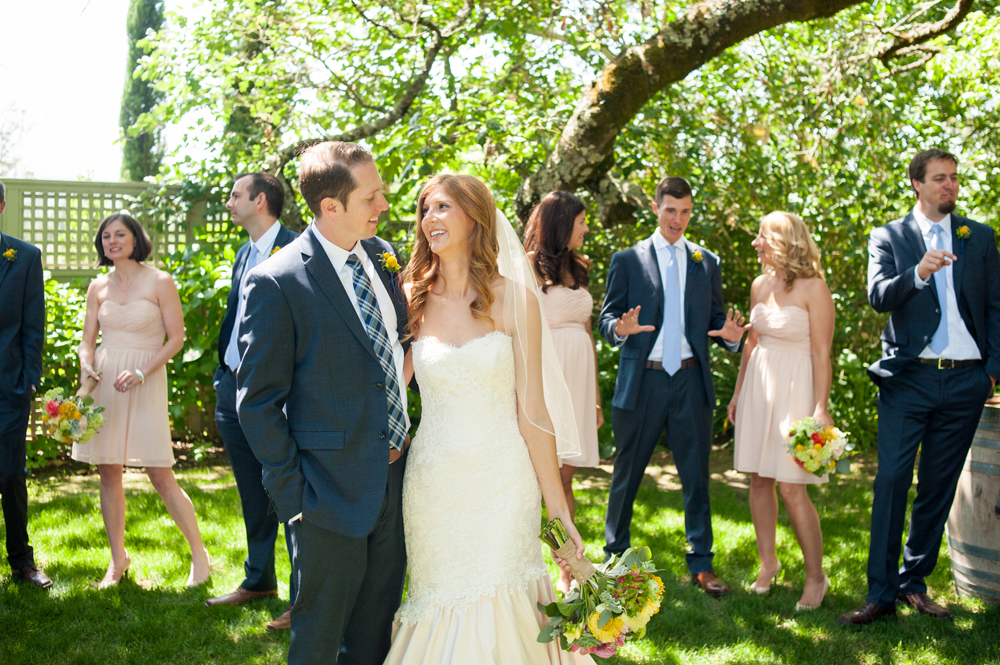 Candid photo of bride and groom in front of their wedding party at the Vine Hill House