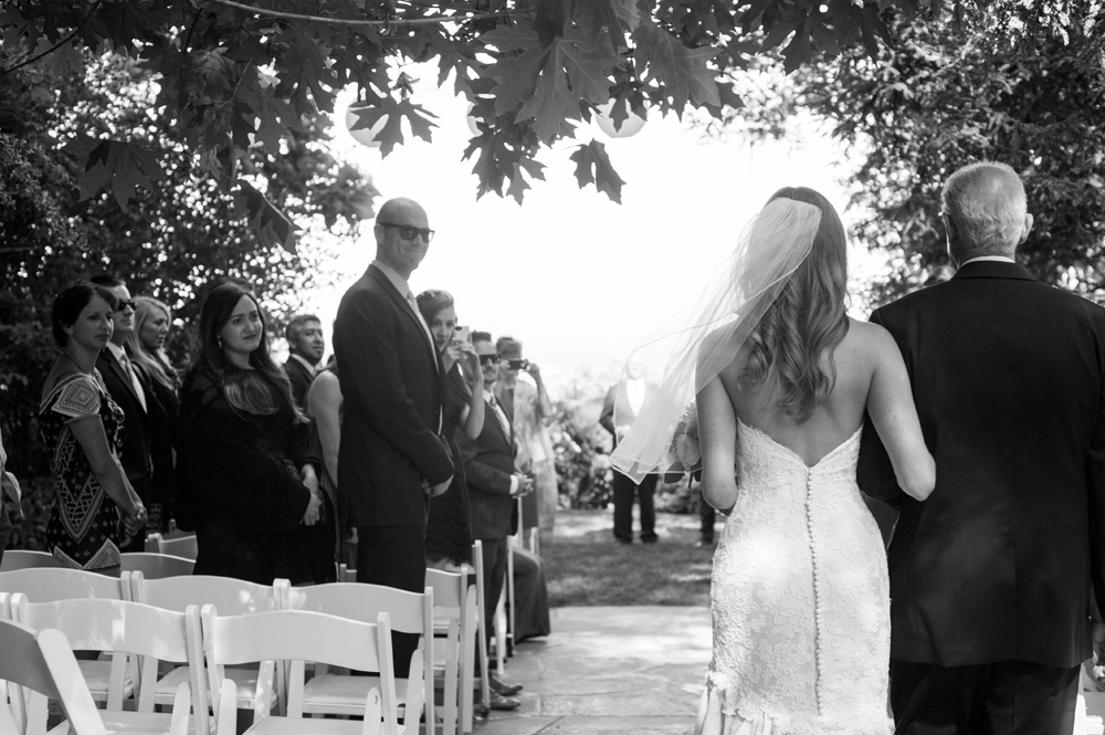 Black and white of bride and her father walking down the aisle during ceremony at the vine hill house