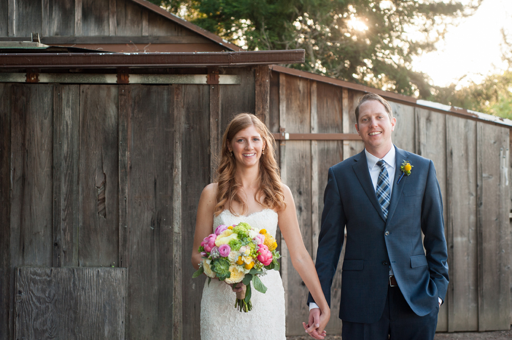 Bride and groom in front of rustic wood barn