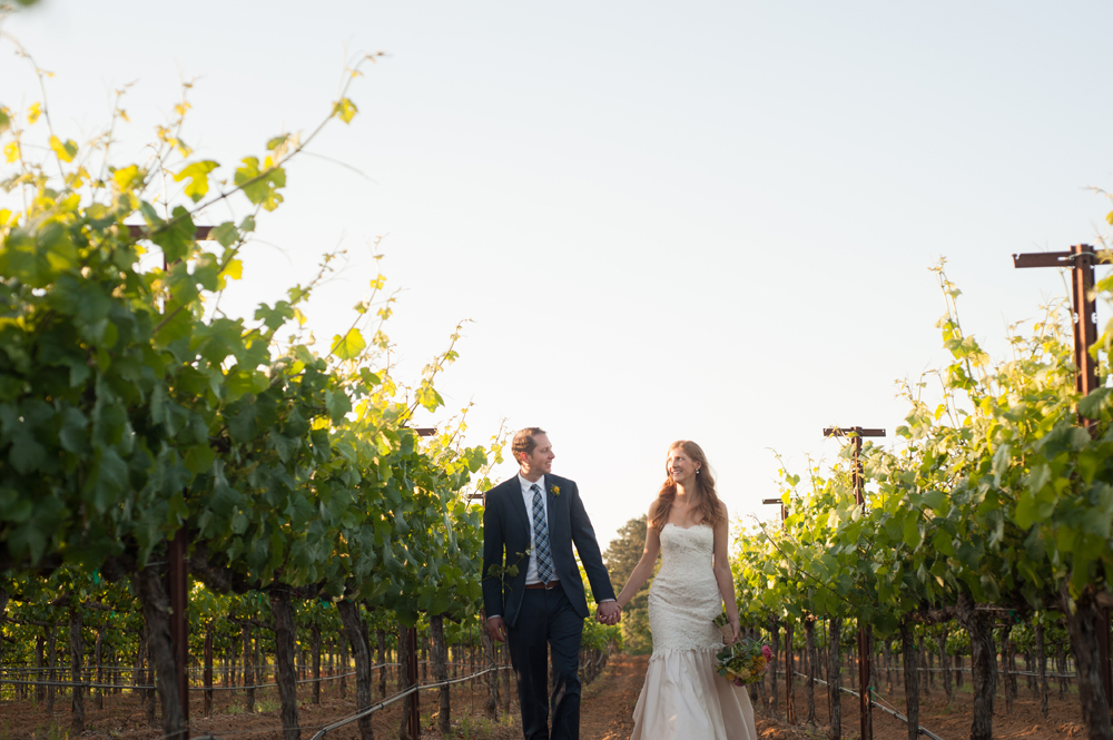 Bride and groom walking down vineyard at the Vine Hill House