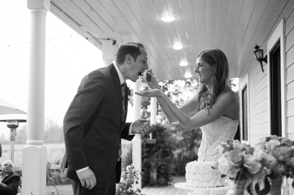 Bride feeding groom a piece of cake on the Vine Hill House porch