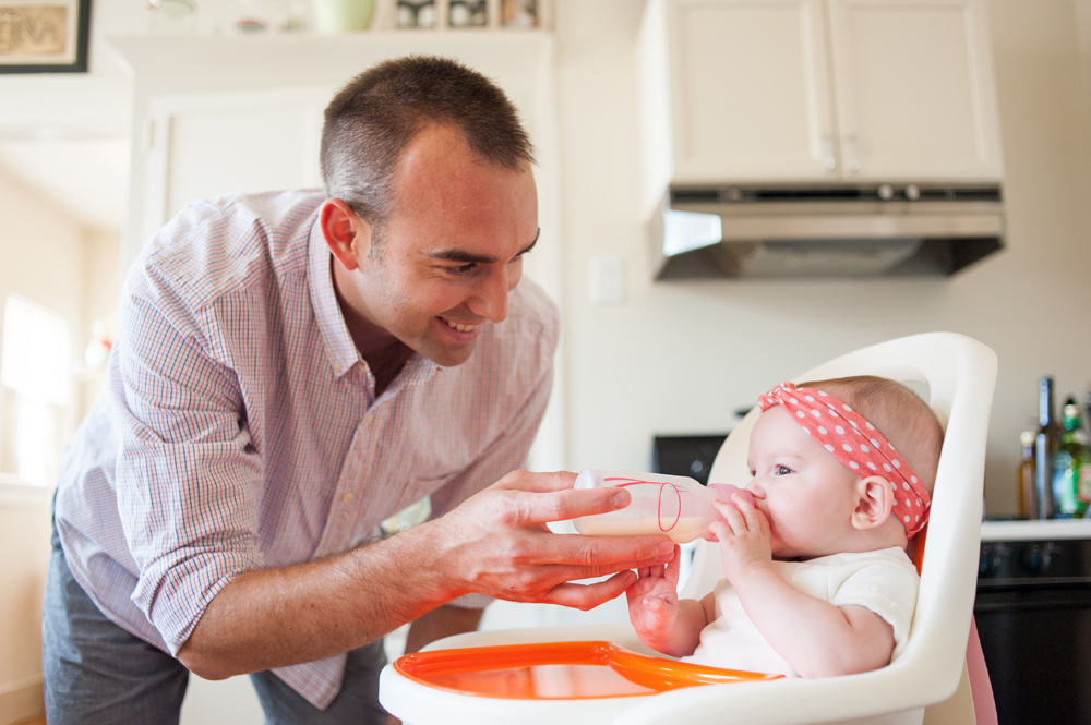 Candid photo of dad feeding bottle to daughter in high chair