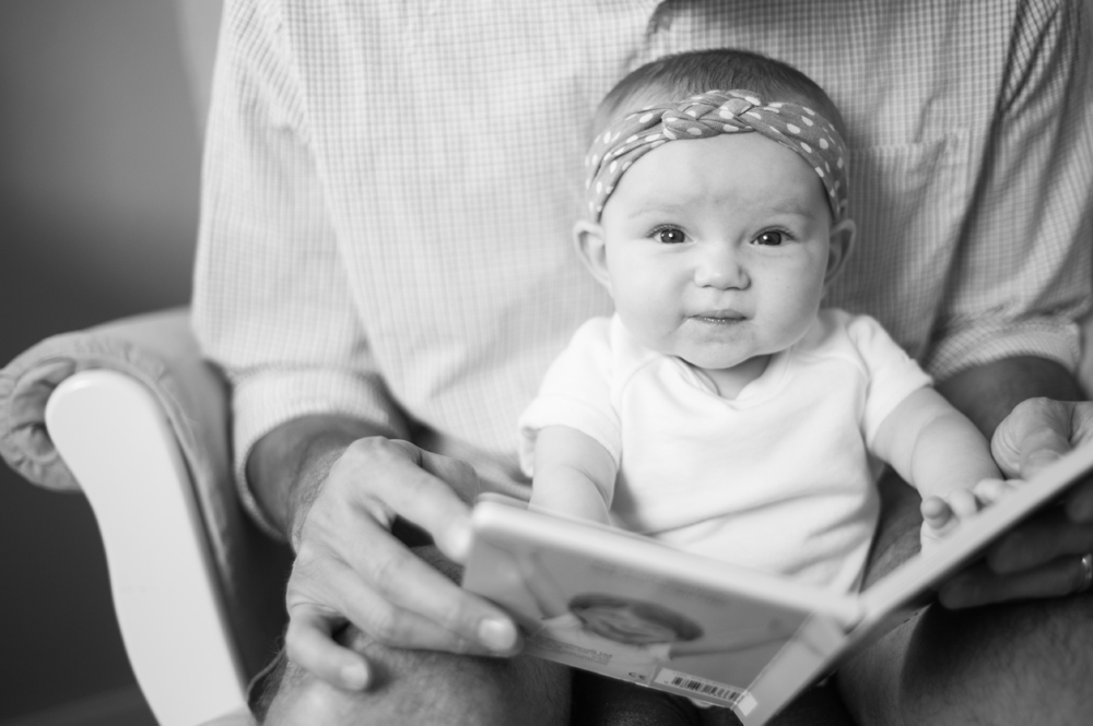 Baby girl reading a book with her dad