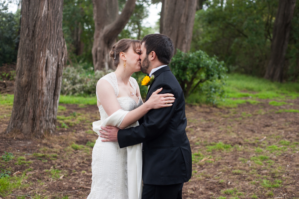 Bride and groom kiss before wedding ceremony in Golden Gate Park