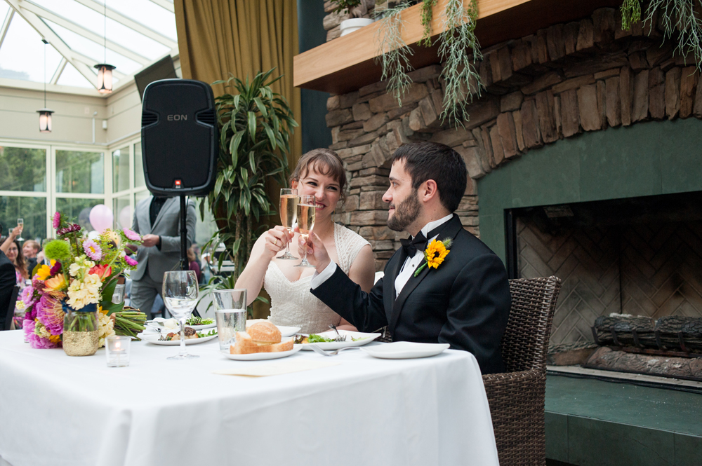 Bride and groom raising their glasses during wedding reception at the Beach Chalet
