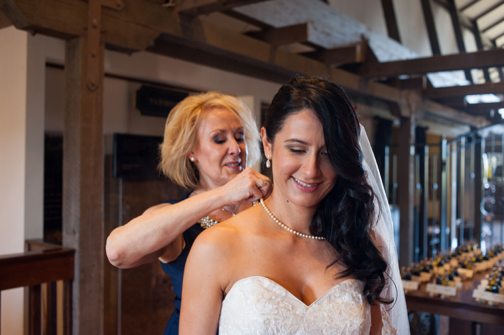 Mother of groom helping bride with necklace
