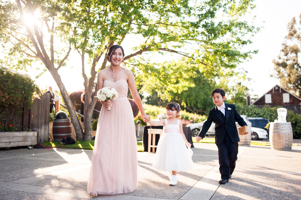 Maid of honor walking with flower girl and ring bearer