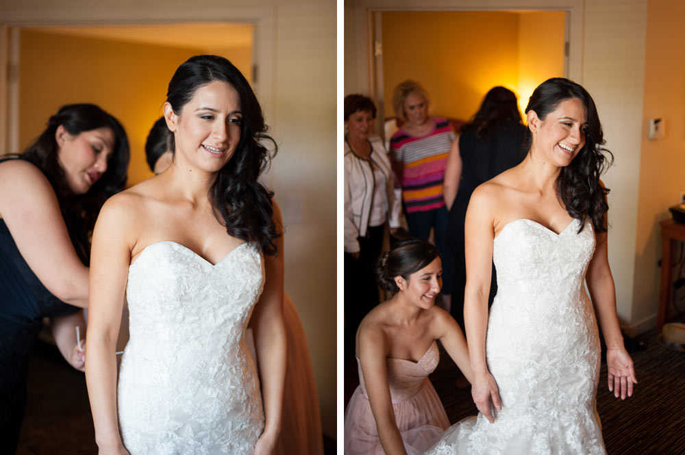 Bride getting into her wedding dress in hotel room