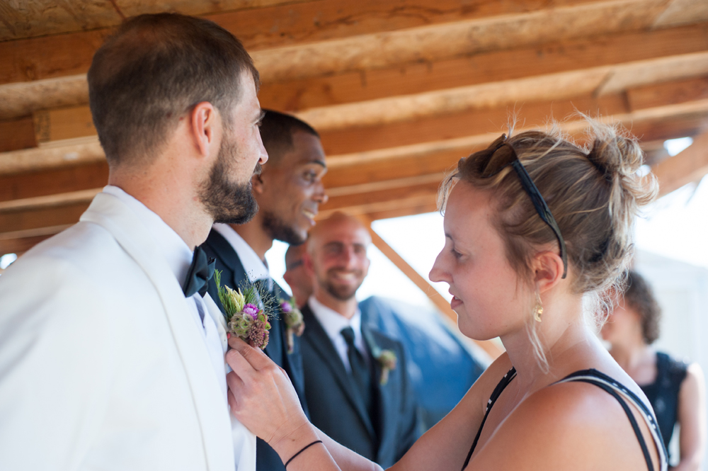 Groom having his boutonniere applied
