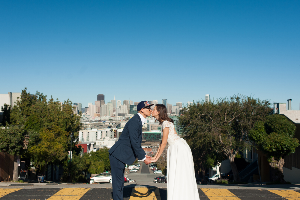 Bride and Groom kiss in crosswalk with San Francisco skyline behind them