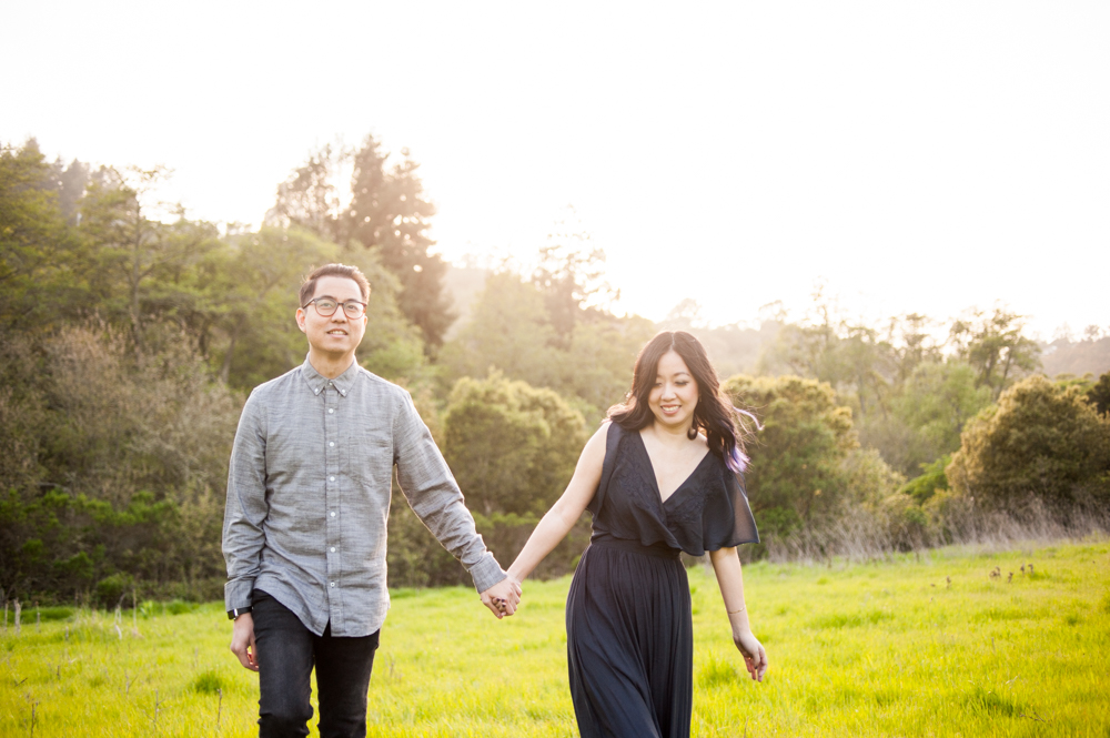 Couple walking in meadow during golden hour in Tilden Park