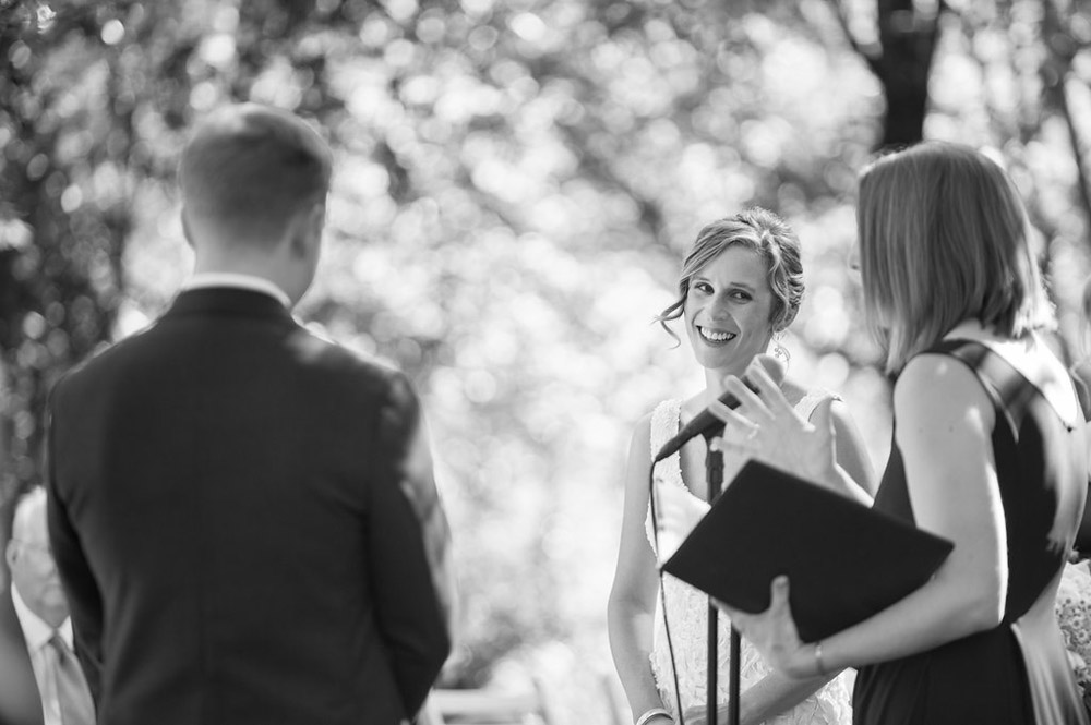 Black and white candid photo of smiling bride during wedding ceremony