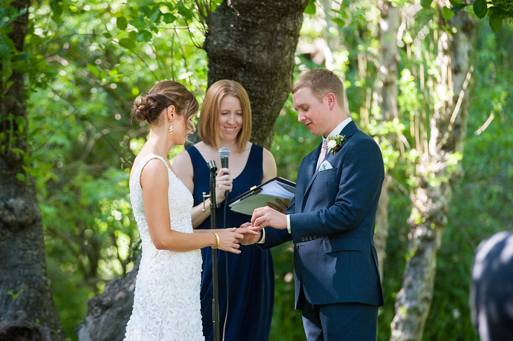 Groom placing wedding ring on Bride's finger