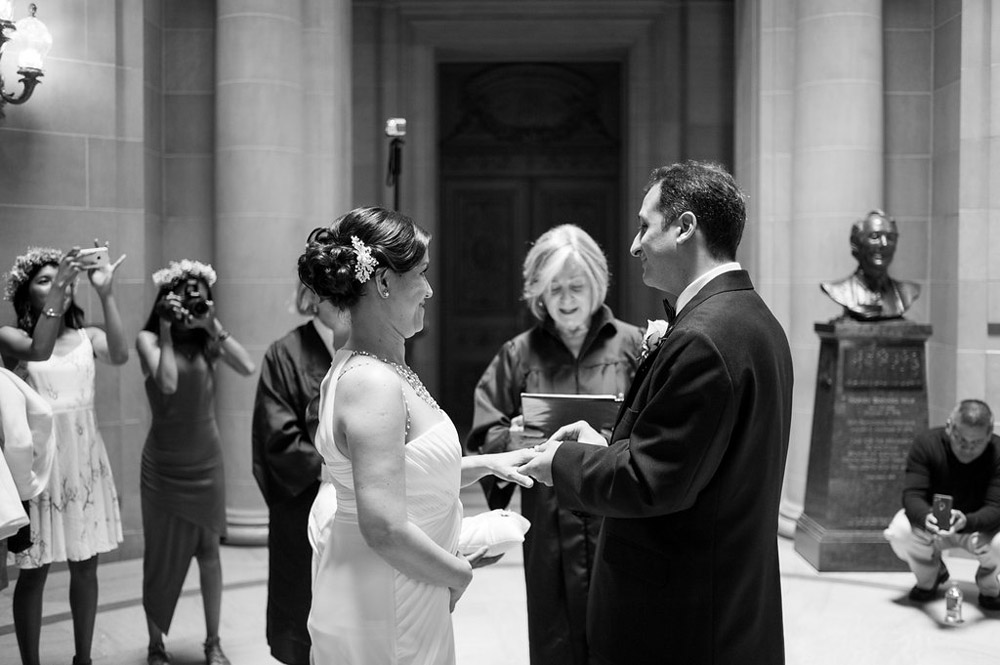 Bride and Groom exchanging rings in City Hall