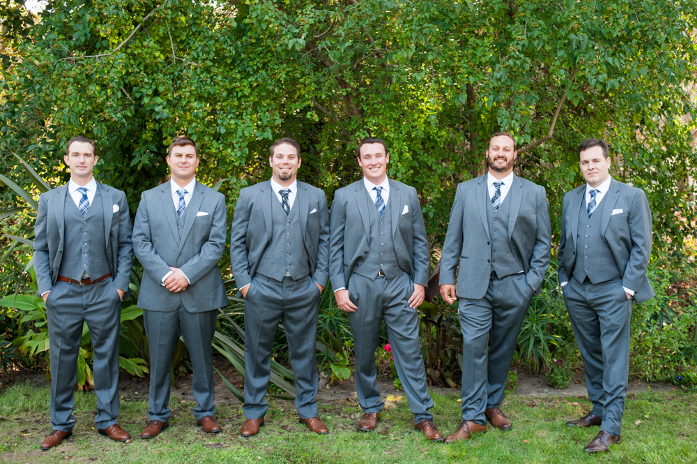 Groomsmen in front of plant wall at Rancho Soquel