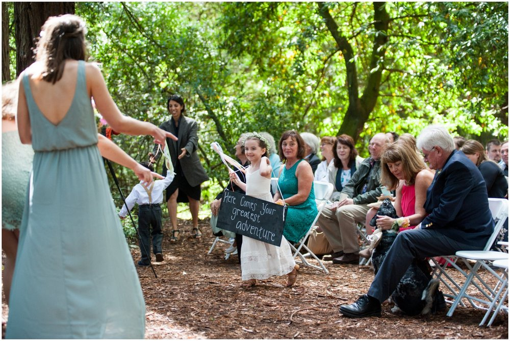 Flower girl walking up aisle at wedding in redwood grove