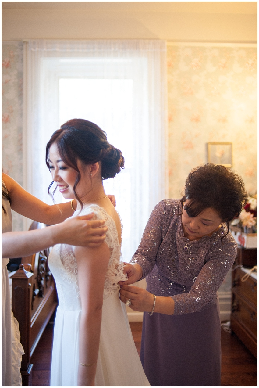 Mother of Bride helping Bride into wedding dress at Elliston Vineyards