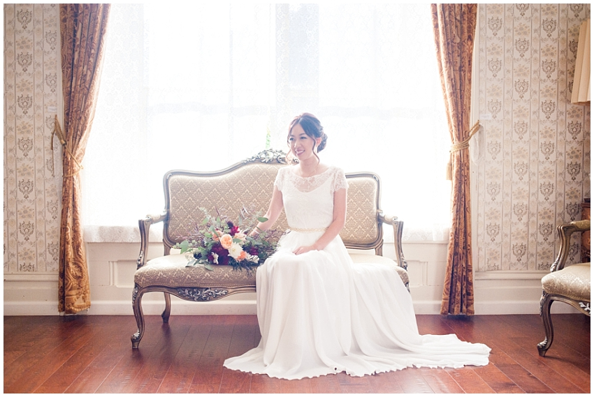 Formal portrait of Bride sitting on vintage couch in Elliston Vineyards