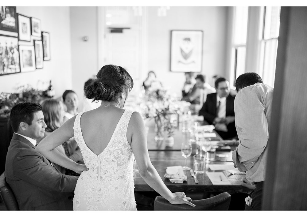 Candid of Bride standing at head of wedding table