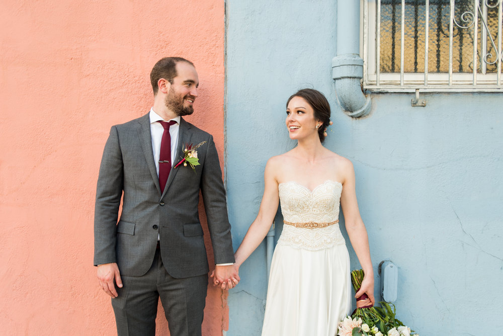 Bride and Groom in front of blue and pink painted wall