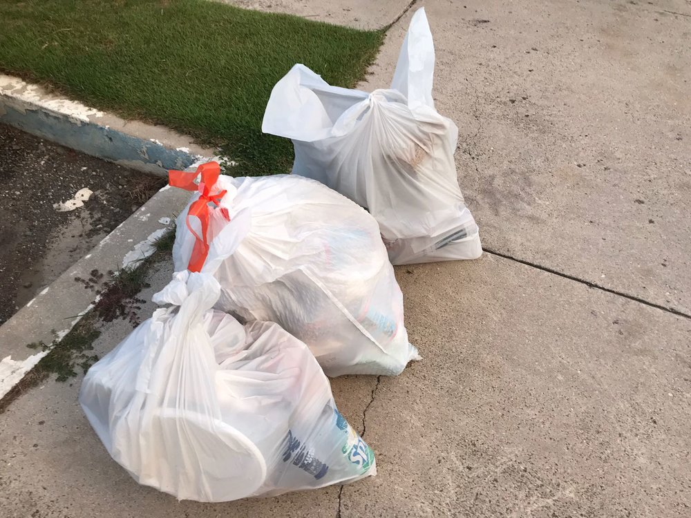 Three full bags of trash left on the beach of Buck Island National Monument by visitors.