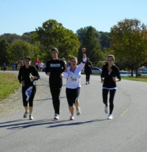 My ankle was killing me, but my support system got me through the last mile of this race. My running group coach, Carol Murray, APR, is on the far left. (Photo credit: Caitlyn Gastonguay)
