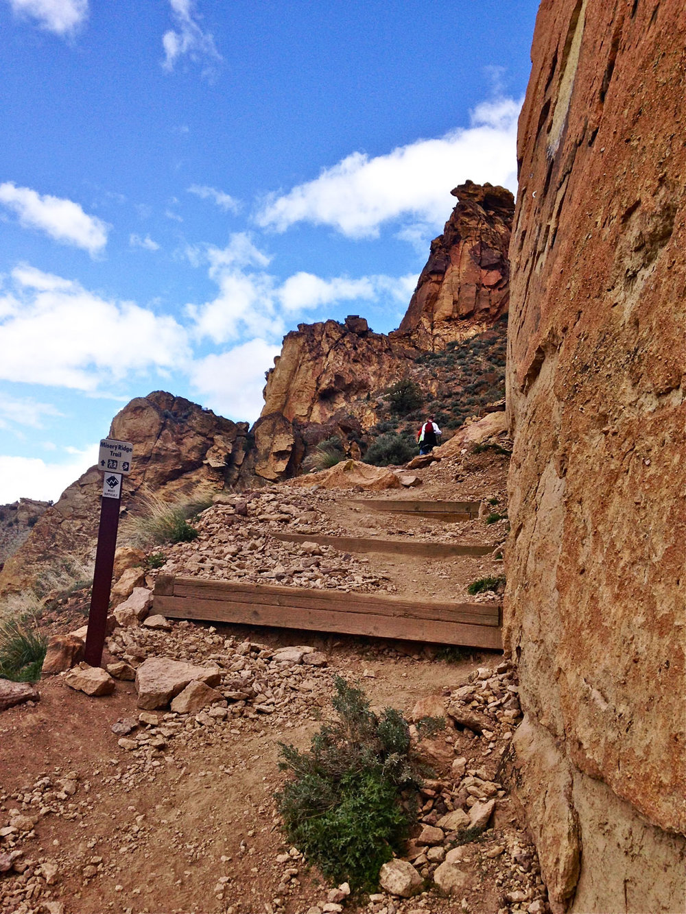 A set of stairs and the sign pointing back up the hill at the base of Monkey Face marks the end to the Misery Ridge Trail at Smith Rock State Park. The loop is completed by joining either leg of the Mesa Verde Trail to the River Trail and back to the bridge.