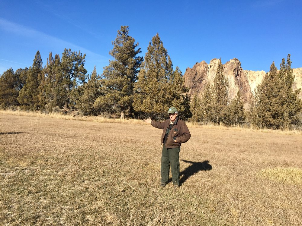 Smith Rock State Park Manager Scott Brown stands in the park property across from the entrance area to the proposed South Point Area parking lot, pointing to where the lot will be situated between two groves of trees ideally for minimal viewing from the road for area neighbors. It will connect to the existing Canyon Trail to the South Bridge as well as to the extended Rim Rock Trail to the Bivy/Campground. Click to enlarge.