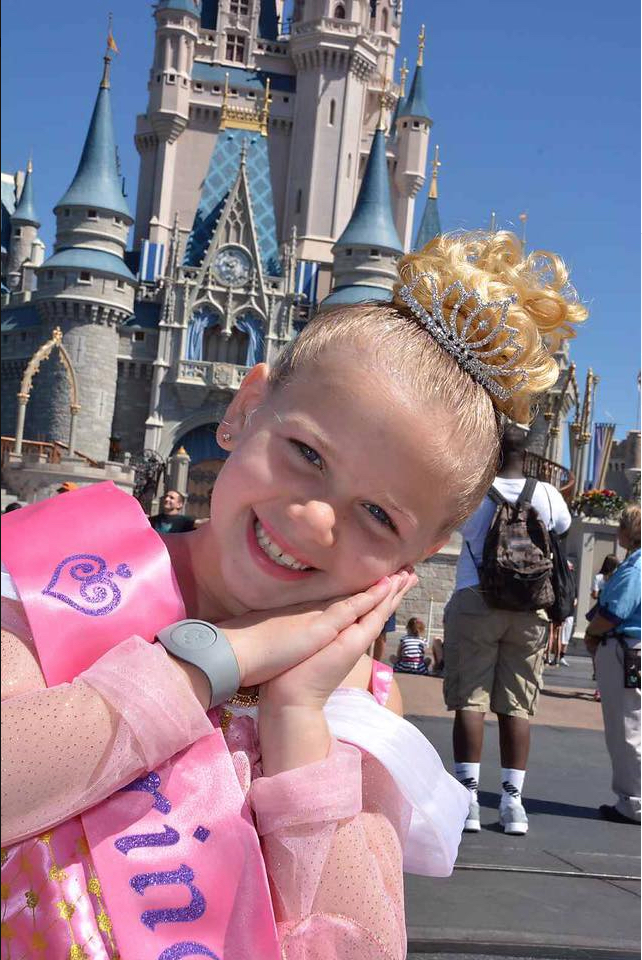 Ava in front of the Magic Kingdom Cinderella Castle after her Character Dresser Princess Package