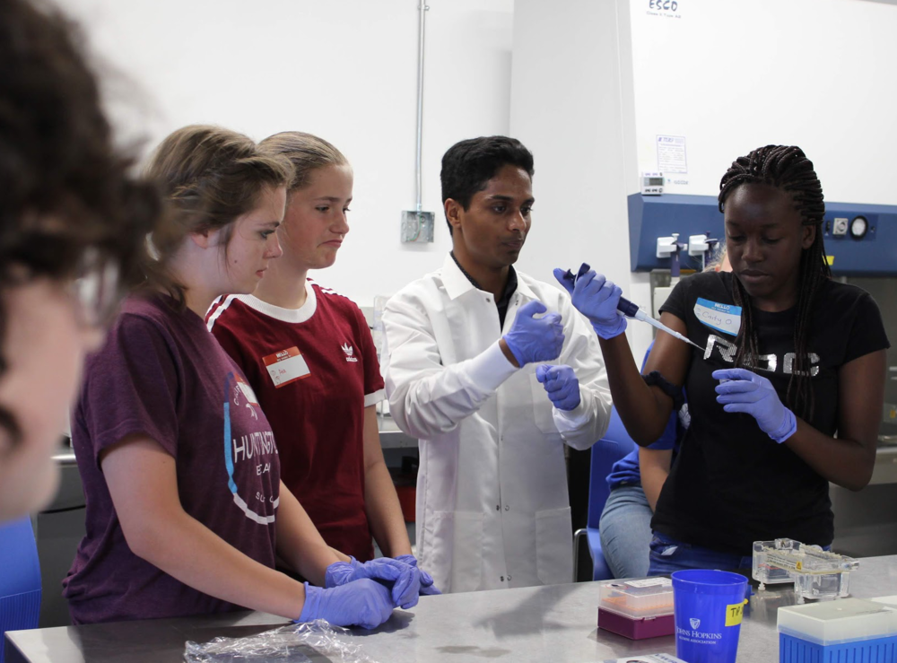 Bioengineering campers learn lab techniques from iGEM expert Keshava.