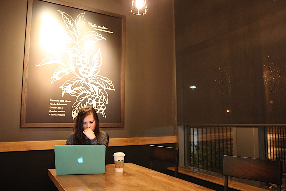 [Image Description: Rikki is sitting at a table in a cafe. Her laptop and coffee sits in front of her on the table.]