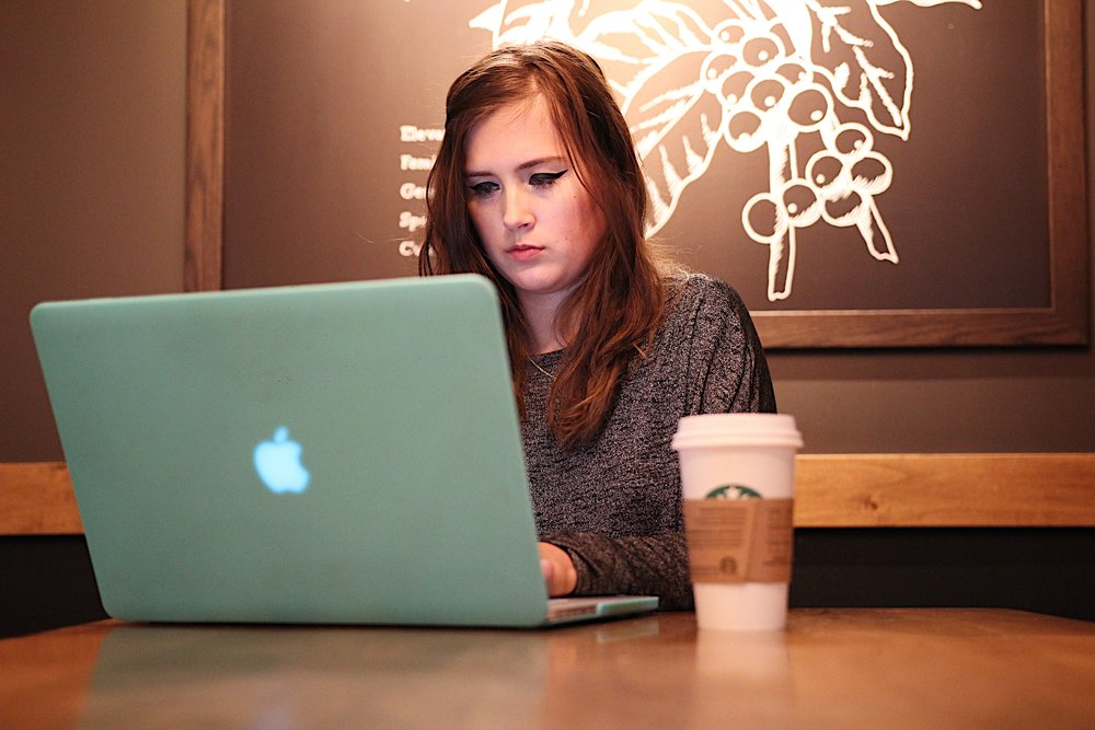 [Image Description: A photo of Rikki sitting at a Starbucks table in front of her laptop and coffee cup. She is seen to be looking down at the laptop screen, typing.]