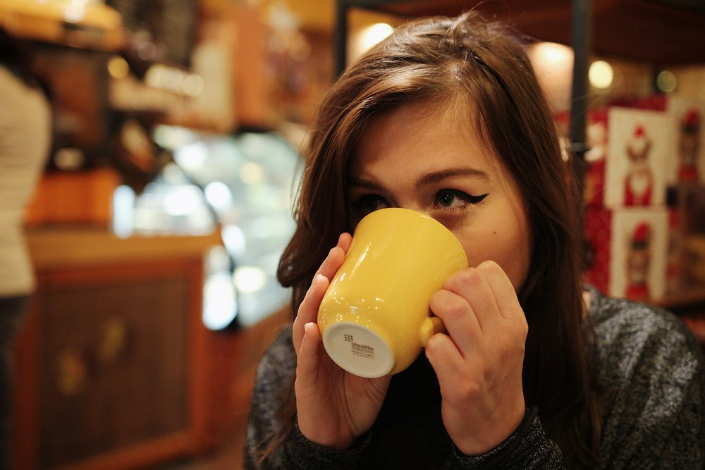 [Image Description: Rikki looking off to the side with a yellow mug held to her mouth.]