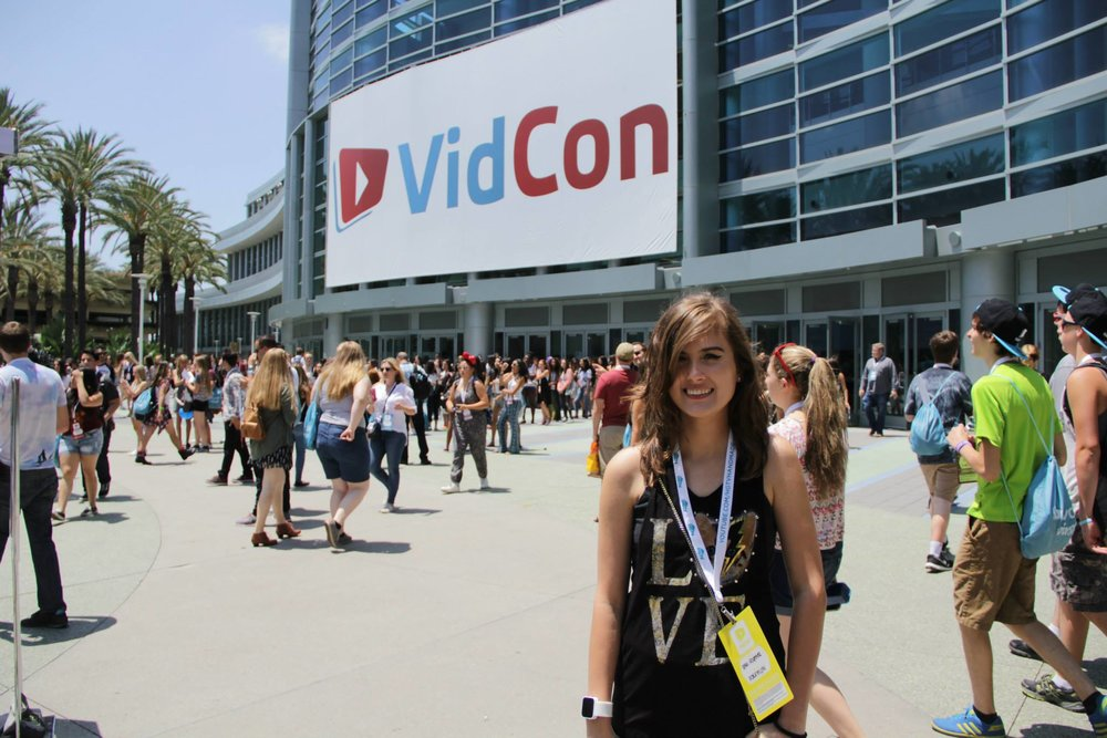 "[Image Description: Rikki is standing in a crowd of people in front of the Anaheim Convention Center, under a big sign that says ""VidCon.""]"