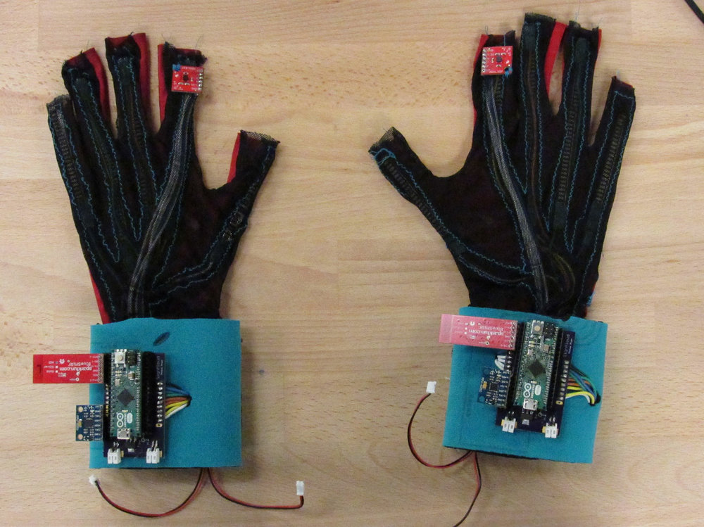 [Image Description: On a light tan table sits a pair of gloves which are black and blue with a miniature motherboard like thing sitting where the wrists would be.]