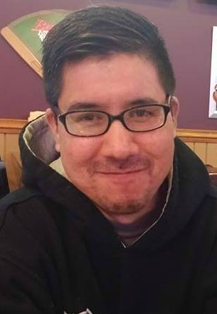[Image Description: A man with short hair, glasses, a bit of facial hair. He is wearing a black hoodie.]