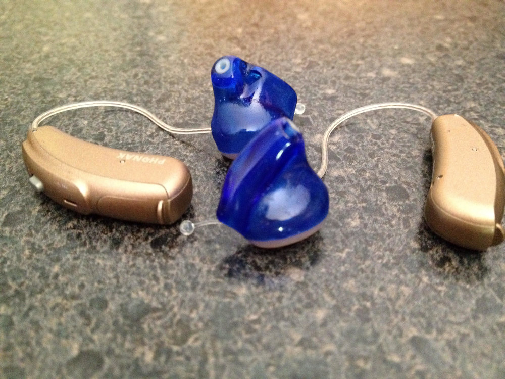 [Image Description: Tan hearing aids with dark blue ear molds sitting on a countertop.]