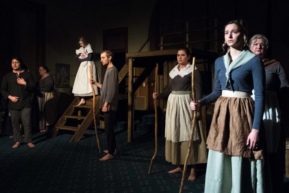 Townspeople (Suellen Weber, Scott Murdock, Megan Hanks, Natalie Power & Beth Kellner) watch as Hester (Leah Christine) descends scaffold.
