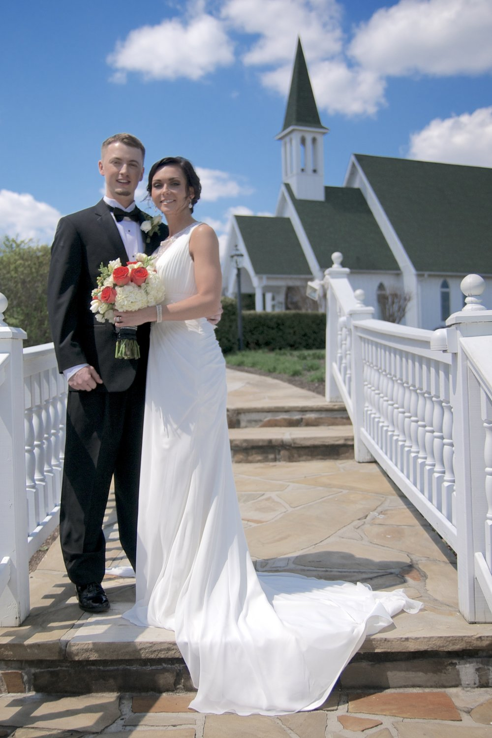 "Small church, black tux, white dress, & red flowers makes this a ""traditional wedding."""