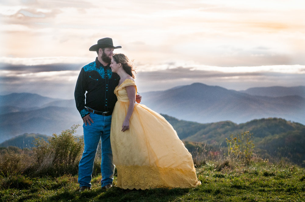 western groom holds his bride close with fall color mountains beyond